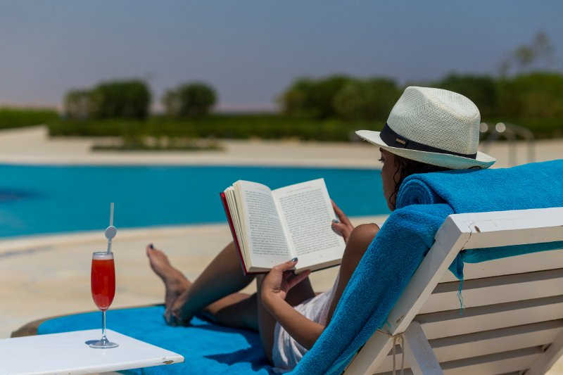 female guest reading a book with a drink and pool view at byoum lakeside hotel in fayoum